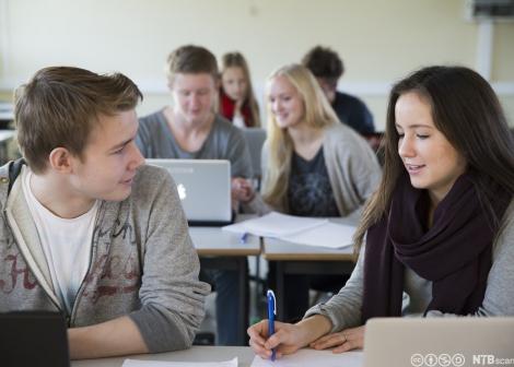 Bildet viser elever i klasserm med pc og skrivesaker foran seg i arbeid, to elever foran er fremhevet